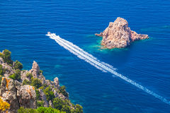 Fast motor boat goes near rocks of Capo Rosso Royalty Free Stock Photography