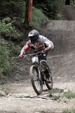 Fast mountain biker racing from ther hill Royalty Free Stock Photography