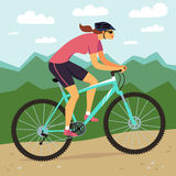 Fast mountain woman biker and mountain landscape. Stock Image