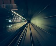 Fast movement of a train through railway tunnels captured from inside the cabin of a train POV stock image