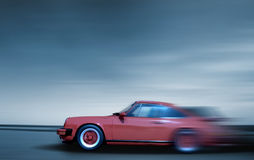 Fast moving car. Red sports car in fast motion in blue tone Royalty Free Stock Photography