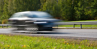 Fast moving car. Fast moving modern car with led lights on highway Royalty Free Stock Photography