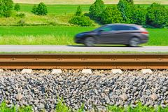 A fast moving car along the road goes alongside the railway tracks Stock Photos