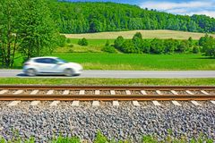 A fast moving car along the road goes alongside the railway trac Stock Image