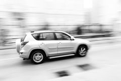 Fast moving car on the city roadway in motion blur Royalty Free Stock Photo
