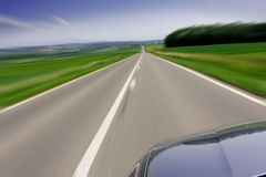 Fast moving car on road. Zooming fast moving car traveling on the road Stock Image