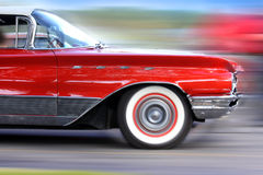 Fast moving classic red car Royalty Free Stock Images