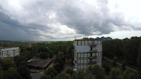 Fast moving dark gray rain clouds time lapse. Against the backdrop of urban development stock footage