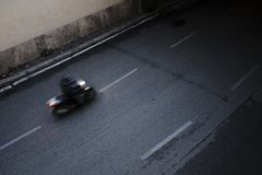 A fast moving motorcyclist going into a tunnel stock photo