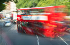 Fast moving red bus in London, framed by trees Royalty Free Stock Photos