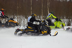 Fast moving riders on snowmobile stock photo