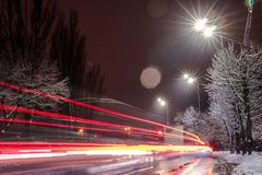 Fast moving traffic at night. winter season. concept of the road, snow and ice removal, danger and safety of movement, street stock image