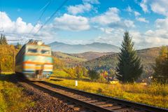 Fast moving train in autumn mountains. Wonderful autumn countryside at sunrise. village down in the valley. beautiful sky over the distant ridge stock images