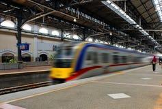 Fast moving train leaving station platform Royalty Free Stock Image