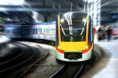 Fast moving train leaving station platform with motion blur Royalty Free Stock Photo