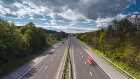 Fast moving vehicles on rural motorway. Speeding vehicles on busy rural motorway at bright sunny day. Time lapse sequence stock footage
