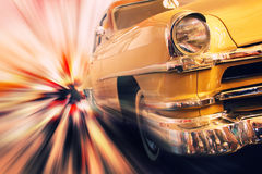 Fast moving vintage car. Gold metallic vintage car in high speed motion Royalty Free Stock Image