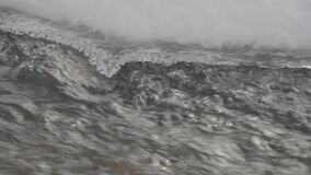 Fast moving water, passing by melting ice. Close-up. Stream in a snowy forest. S-Log