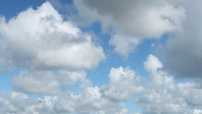 Fast moving white clouds in blue sky timelapse. Stock Photo