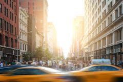 Fast-paced life in New York City street scene with cabs driving down 5th Avenue and crowds of people in New York City. Fast-paced life in New York City street Royalty Free Stock Photo
