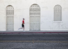 Fast paced man runs down city street. Royalty Free Stock Images