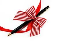 Fast penna som en gåva med den röda pilbågen Fotografering för Bildbyråer