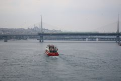 Fast red boat floating to Golden Horn Metro Bridge royalty free stock photos