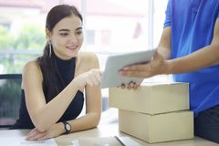 Fast and reliable service. Caucasian woman signing on tablet pc computer at home office. Delivery man brings delivering parcel box. Fast and reliable service royalty free stock image