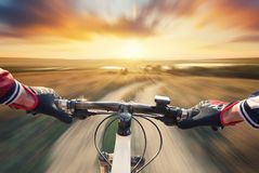 Fast ride on bike in mountain valley during sunset. Sport and active life concept royalty free stock photography