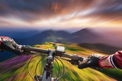 Fast ride on bike in mountain valley during sunset. Sport and active life concept stock photos