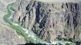 Fast river runs through a rocky canyon. On the banks of the river grow different green trees and bushes. A long canyon with a beautiful view of the river. Blue stock video footage