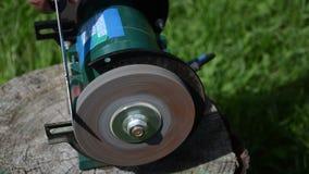 Fast rotating black sharpener wheel hand sharpening large blade stock video