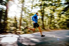 Fast running man runner. In forest road blurred motion Royalty Free Stock Image