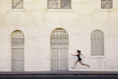 Fast running woman on a city street. Royalty Free Stock Photos