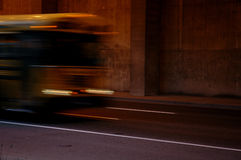Fast School Bus Blur. A school bus traveling through a concrete underpass at night with blur royalty free stock images