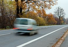 Fast silver car on a straight road. Fast blurred silver car on a straight road during autumn Royalty Free Stock Photography