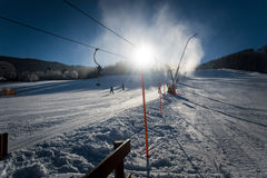 Fast ski slope with working snow cannons at sunny day Royalty Free Stock Photos