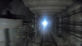 Fast speed underground train riding in a tunnel of the modern city. Time lapse of subway train moving at dark tunnel