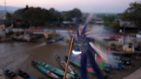 Flower wind vane, Inle Lake, Myanmar. The fast spinning flower wind vane on the balcony with a view on canoe port of Nyaungshwe - tourist village, located next stock video footage