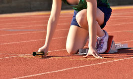 Fast start. Track runner in starting blocks ready to carry relay baton Royalty Free Stock Photo