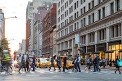 Fast stegade gataplats med folk som går över genomskärning i New York City royaltyfri fotografi