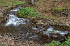 A fast stream in mountainous terrain. Water flowing in the river shown in a long exposure. Season of the spring stock photography