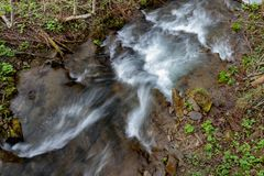 A fast stream in mountainous terrain. Water flowing in the river shown in a long exposure. Season of the spring stock photo