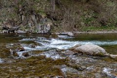 A fast stream in mountainous terrain. Water flowing in the river shown in a long exposure. Season of the spring royalty free stock photography