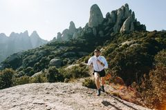 Athletic strong man runs trail ultra marathon. Fast and strong, fit athletic man runs on mountain path or trail during ultra marathon race, hard training workout Royalty Free Stock Photography