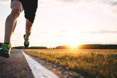 Fast strong runner feet running on asphalt road close up in sport shoe. Athlet run outdoor. Blurred background stock images