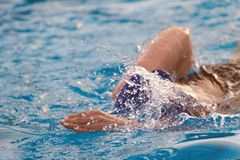 Fast swimming woman. In blue pool water. Swim competition Royalty Free Stock Photos