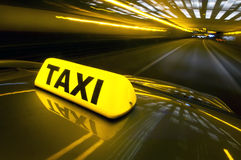 Fast taxi. A cab at high speed on a motorway in an urban area with the lit taxi sign on top of its roof royalty free stock photography