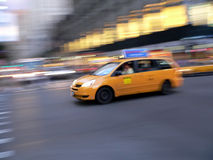 Fast taxi cab mini van in New York City. A fast taxicab minivan style races through New York City Stock Images
