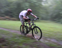 Fast Track. A biker speeds through a single track filled with water stock photography